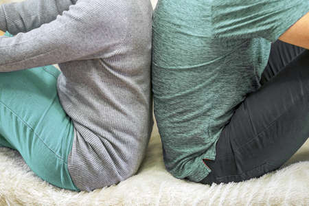 Couple with their backs turned to each other sitting on white couch. Angry and upset couple turning their back on each other in bed.