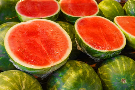 Watermelon cut into halves on the counter of the village fair. Pile of green watermelons, a market bench for a watermelon merchant, cut red watermelons lie on top