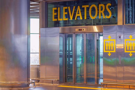 View of the lift doors in the airport office building. Wide angle view of a modern elevator with glass closed doors. Elevators in the modern lobby