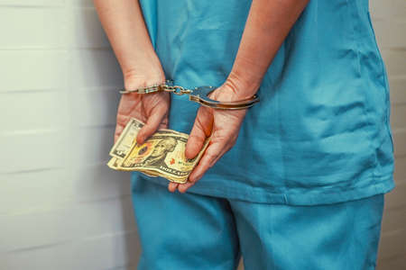 Crime in medicine, surgeon or doctor in blue uniform with handcuffed hands holding a bribe. Criminal medic woman hands locked in handcuffs. Back view