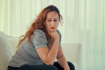 Sad woman. Woman sitting in the room looking to the side. Woman depression or domestic violence. People, grief and domestic violence concept. Coseup of unhappy female.