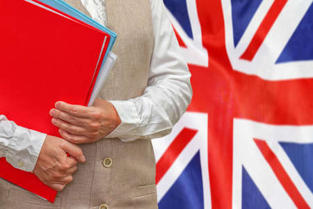 Woman holding red folder on United Kingdom flag background. Education and jurisprudence concept in UK 免版税图像