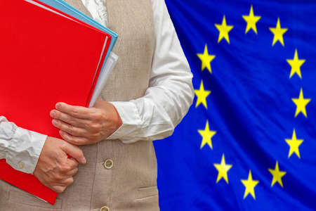 Woman holding red folder on European Union flag background. Education and jurisprudence concept in EU 免版税图像