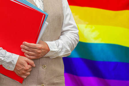 Woman holding red folder on LGBT flag background. Education and jurisprudence concept for LGBT 免版税图像