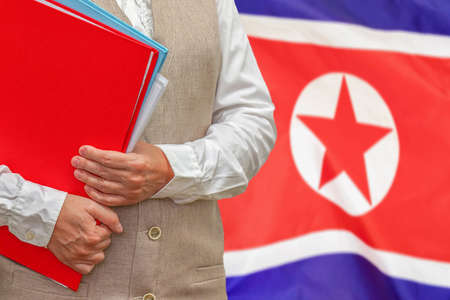Woman holding red folder on North Korea flag background. Education and jurisprudence concept in North Korea