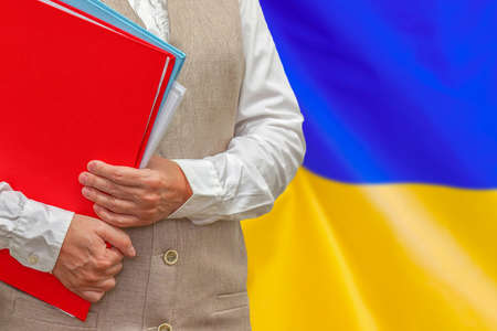 Woman holding red folder on Ukraine flag background. Education and jurisprudence concept in Ukraine