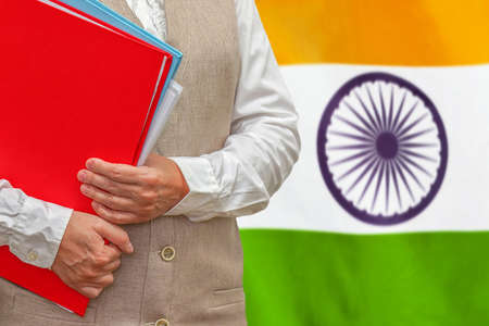 Woman holding red folder on India flag background. Education and jurisprudence concept in India 免版税图像