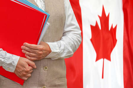 Woman holding red folder on Canada flag background. Education and jurisprudence concept in Canada