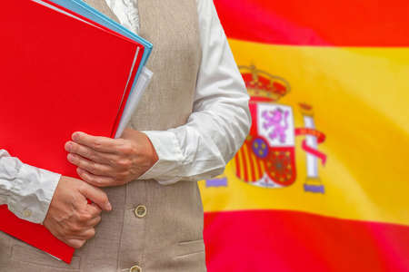 Woman holding red folder on Spain flag background. Education and jurisprudence concept in Spain