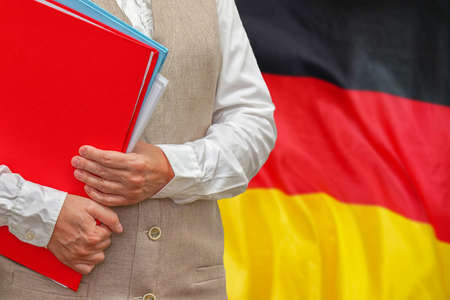 Woman holding red folder on Germany flag background. Education and jurisprudence concept in Germany