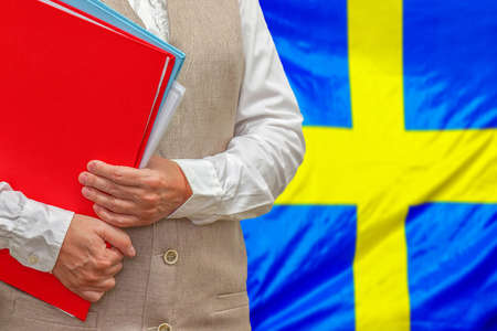 Woman holding red folder on Sweden flag background. Education and jurisprudence concept in Sweden