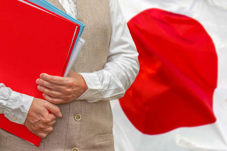 Woman holding red folder on Japan flag background. Education and jurisprudence concept in Japan