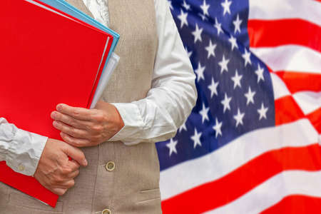 Woman holding red folder on USA flag background. Education and jurisprudence concept in US