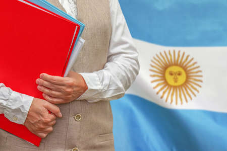 Woman holding red folder on Argentina flag background. Education and jurisprudence concept in Argentina 免版税图像