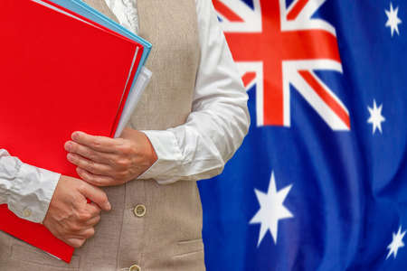 Woman holding red folder on Australia flag background. Education and jurisprudence concept in Australia