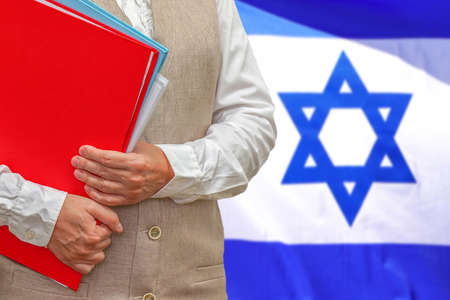 Woman holding red folder on Israel flag background. Education and jurisprudence concept in Israel 免版税图像