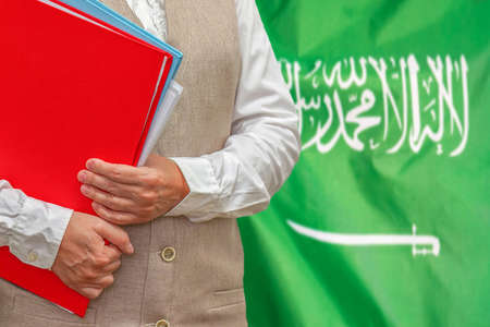 Woman holding red folder on Saudi Arabia flag background. Education and jurisprudence concept in Saudi Arabia