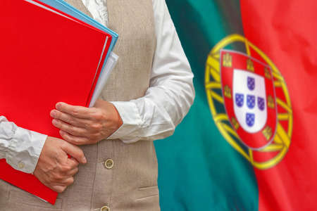 Woman holding red folder on Portugal flag background. Education and jurisprudence concept in Portugal 免版税图像