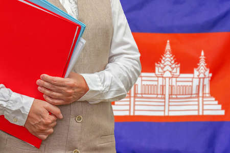Woman holding red folder on Cambodia flag background. Education and jurisprudence concept in Cambodia