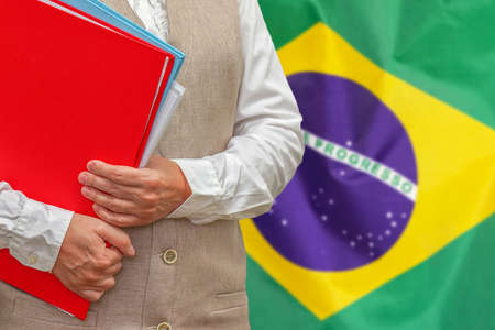Woman holding red folder on Brazil flag background. Education and jurisprudence concept in Brazil