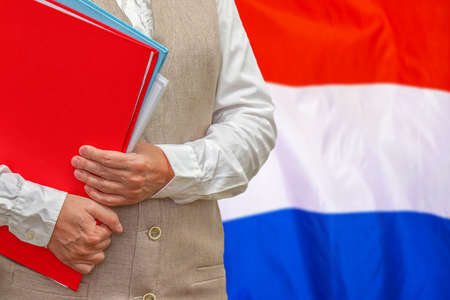 Woman holding red folder on Netherlands flag background. Education and jurisprudence concept in Netherlands
