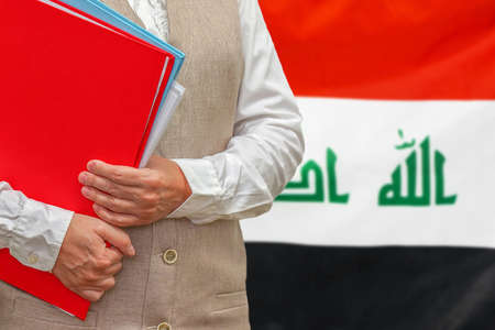 Woman holding red folder on Iraq flag background. Education and jurisprudence concept in Iraq 免版税图像