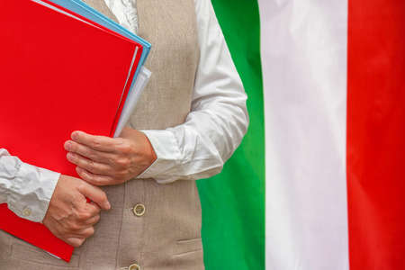 Woman holding red folder on Italy flag background. Education and jurisprudence concept in Italy 免版税图像