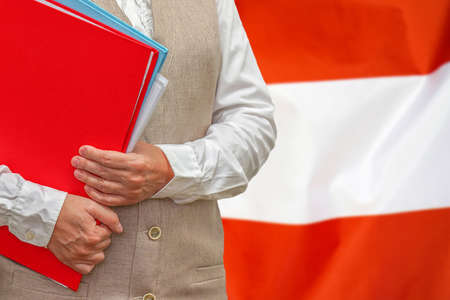 Woman holding red folder on Austria flag background. Education and jurisprudence concept in Austria 免版税图像