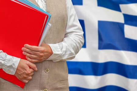 Woman holding red folder on Greece flag background. Education and jurisprudence concept in Greece