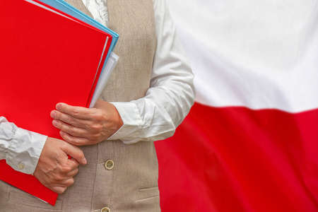 Woman holding red folder on Poland flag background. Education and jurisprudence concept in Poland