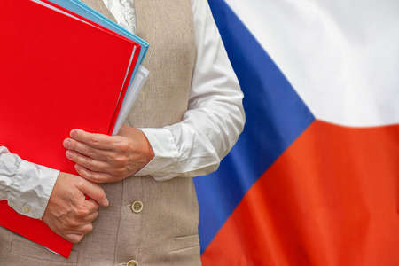 Woman holding red folder on Czech Republic flag background. Education and jurisprudence concept in Czech Republic