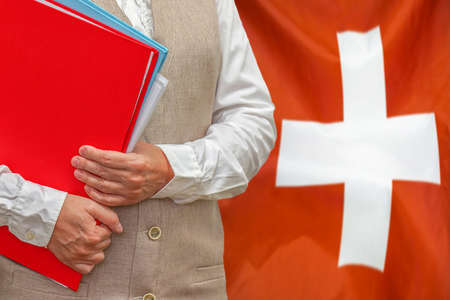 Woman holding red folder on Switzerland flag background. Education and jurisprudence concept in Switzerland
