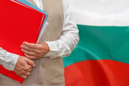 Woman holding red folder on Bulgaria flag background. Education and jurisprudence concept in Bulgaria