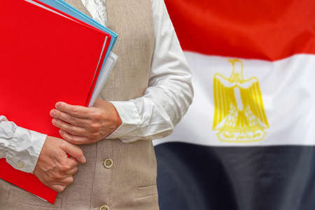 Woman holding red folder on Egypt flag background. Education and jurisprudence concept in Egypt 免版税图像