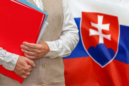 Woman holding red folder on Slovakia flag background. Education and jurisprudence concept in Slovakia