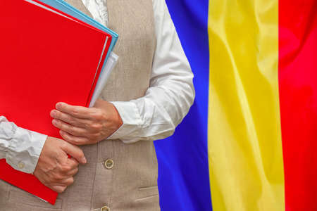 Woman holding red folder on Moldova flag background. Education and jurisprudence concept in Moldova