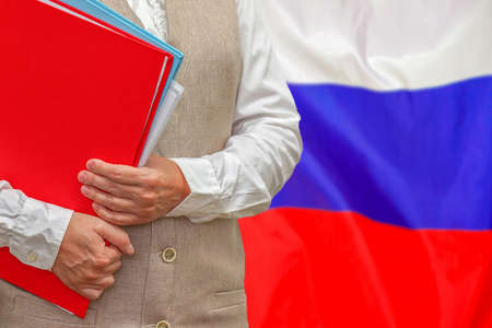 Woman holding red folder on Russia flag background. Education and jurisprudence concept in Russia