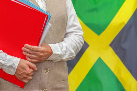 Woman holding red folder on Jamaica flag background. Education and jurisprudence concept in Jamaica