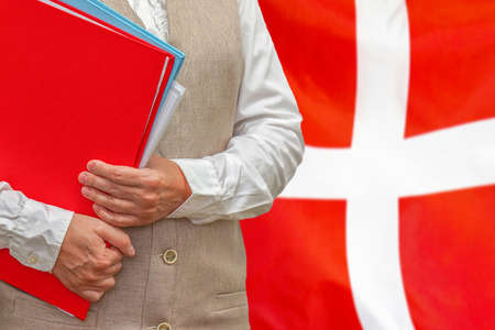 Woman holding red folder on Denmark flag background. Education and jurisprudence concept in Denmark