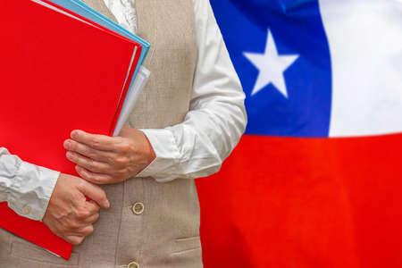 Woman holding red folder on Chile flag background. Education and jurisprudence concept in Chile
