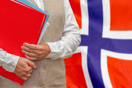 Woman holding red folder on Norway flag background. Education and jurisprudence concept in Norway