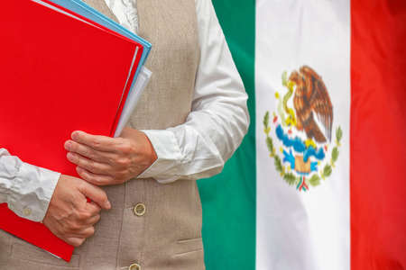 Woman holding red folder on Mexico flag background. Education and jurisprudence concept in Mexico