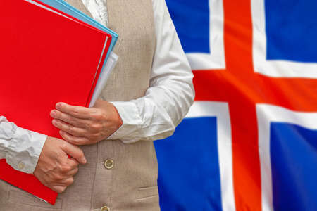Woman holding red folder on Iceland flag background. Education and jurisprudence concept in Iceland