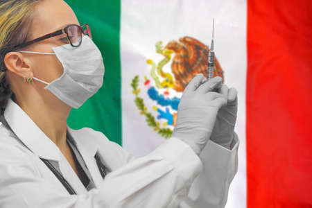 Female doctor or nurse in gloves holding syringe for vaccination against the background of the Mexico flag. Medicine concept and fight the virus. Coronavirus in Mexico.