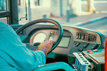 Concept of bus driver steering wheel and driving passenger bus. Hands of driver in a modern bus by driving Standard-Bild
