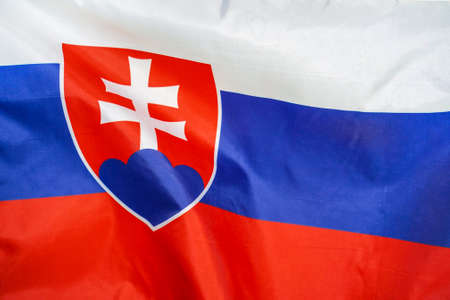 Fabric texture flag of Slovakia. Flag of Slovakia waving in the wind. Slovakia flag is depicted on a sports cloth fabric with many folds. Sport team banner Foto de archivo