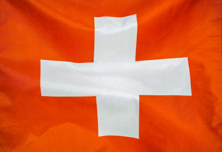 Fabric texture flag of Switzerland. Flag of Switzerland waving in the wind. Switzerland flag is depicted on a sports cloth fabric with many folds. Sport team banner Foto de archivo