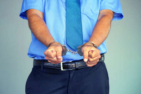Arrested man handcuffed hands. Businessman in office in handcuffs holding a bribe. Arrested man in handcuffs. Criminal hands locked in handcuffs Foto de archivo