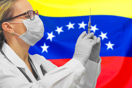 Female doctor or nurse in gloves holding syringe for vaccination against the background of the Venezuela flag. Medicine concept and fight the virus. Coronavirus in Venezuela