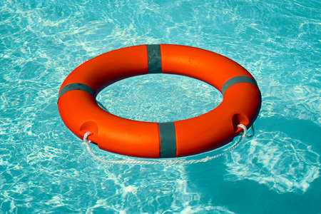 Red lifebuoy pool ring float on blue water. Life ring floating on top of sunny blue water. Life ring in swimming pool Foto de archivo